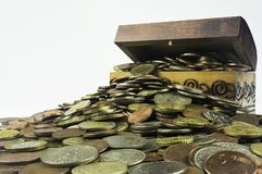 Close-up of a treasure chest which is bursting with coins on a w Stock Images