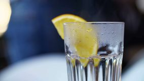 Close up Treatment of Flu. Transparent cup of warm water with lemon.  stock video footage