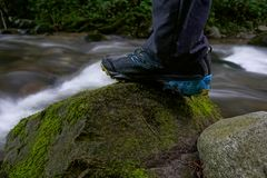 Hiking shoes, close up hiker outdoors walking crossing river, creek Royalty Free Stock Image