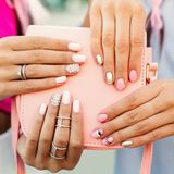 Close up of bag with girls hands with manicure over it.