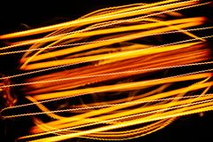 Close Up of a tungsten filament light bulb. Light streaks for back. Ground Stock Photo