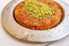 Turkish Künefe, Hot and Cheesy Southeastern Dessert. Close up Turkish Künefe, Hot and Cheesy Southeastern Dessert royalty free stock photo