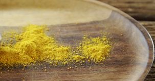 Turmeric powder in spoon on a plate 4k. Close-up of turmeric powder in spoon on a plate 4k stock footage