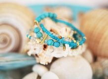 Close up of turquoise and agate gemstone bracelets. Blurry background with shells stock photography