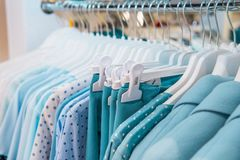 Close up turquoise color Clothes on hangers in shop, butique. Make Outfit set. Shopping Mall. Shopper. Sales. Shopping Center. Sel. Ective focus Stock Photo