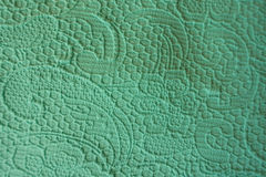 Close-up of turquoise fabric with raised pattern with flowers and squiggles. Close up of turquoise fabric with raised pattern with flowers and squiggles Stock Photography