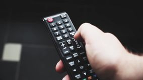 Close up of TV remote changing channels. Channel surfing, focused on the hand and remote control stock footage