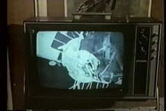 Close-up of TV screen broadcasting astronaut working on spacecraft stock footage