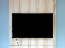 Close up of TV set on wooden wall hanging above bench in office. Concept of waiting room interior in luxury establishment Royalty Free Stock Photo