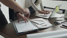 Close-up Twee architecten die met laptop, kompassen en tekeningen voor een architecturaal plan werken stock footage