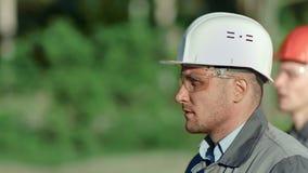 Close-up twee professionele metaalarbeider in helm en glazen lopen openlucht bij productie-installatie stock video