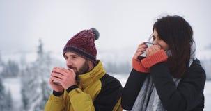 Close-up twee vrienden drinkt hete thee van ijzerkop in verbazende plaats, met de winterberg en sneeuwbos stock footage