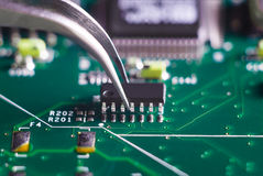 Close up on tweezers holding chip on computer circuit board Royalty Free Stock Images