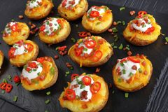 Close-up of twice baked potatoes halves. Close-up of twice baked potato halves loaded with grated cheddar cheese, bacon, chili peppers slices, sour cream and Stock Photo