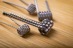 Close up twisted coils for e cig or electronic cigarette for vape devices, RDA prebuild coil clapton over a wooden background. stock images