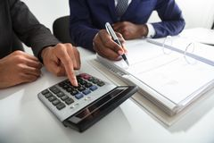 Two Accountants Calculating Tax Invoice Using Calculator Royalty Free Stock Photography