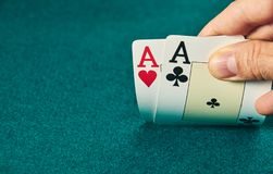 Close-up of two aces held in one hand on the green game mat on the right side of the image to leave room for editing. Stack, poker, luck, table, leisure stock photo