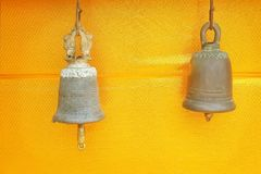 Two ancient brass bells hanging on gold fabric background at temple in Thailand stock images