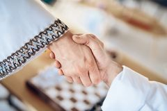 Close up handshake with chessboard in background. royalty free stock photos