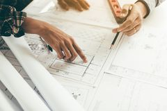 Close up two architect hands holding pencil and pointing on building blueprints in office room. stock photography