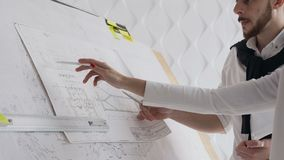 Close-up of two architects discussing a project to build a new project depicted drawings of which are depicted on a