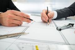 Close-up of two architects working on blueprint Stock Photos