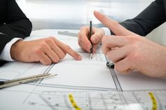 Close-up of two architects working on blueprint Royalty Free Stock Images