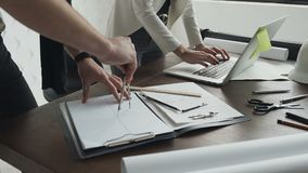 Close-up.Two architects working with a laptop, compasses and drawings for an architectural plan. Close-up Two architects working with a laptop, compasses and stock footage