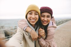 Close up of two asian women standing together outdoors. Cheerful asian women in winter wear standing near the sea on a cold morning. Smiling women standing royalty free stock photo