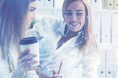 Two colleagues drinking coffee in office, graphs Stock Photography