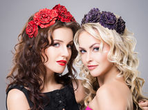 Close-up of two attractive, young ladies wearing flower alike accessories Stock Photography