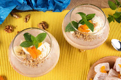 Close-up of two banana smoothies in dessert glasses, Turkish Delight and dried apricots with walnuts on a colored Royalty Free Stock Photos
