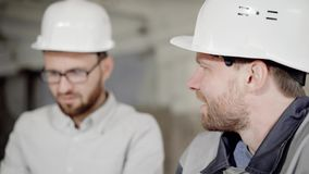 Close up of two bearded men in protective helmets working together in construction area. Foreman and worker are standing. On building site investigating stock video footage