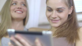 Close up of two beautiful excited women using tablet pc in the living room. Two beautiful young women at home sitting on sofa  using a tablet PC computer and stock video