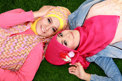 Close up of two beautiful happy muslim woman lying on grass Stock Image