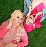 Close up two beautiful happy muslim woman lying on grass Stock Image