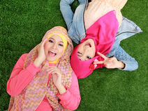 Close up two beautiful happy muslim woman lying on grass Royalty Free Stock Images