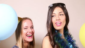 Close up of two beautiful women dancing and laughing in party photo booth stock footage