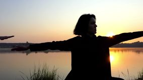 Two Young Women do Yoga Exercise on The Gorgeous Lake Bank at Sunset. A Close up of Two Beautiful Young Women Practicing a Warrior Yoga Exercise. They Finish it stock video footage