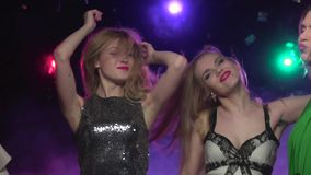 Close-up of two blonde girls dancing at party. Slow motion