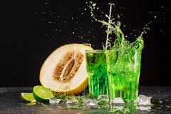 Close-up of two bright tarragon  splashing cocktails on a black background. Drinks with tarragon, cut sweet melon, ice cubes, and Stock Photos