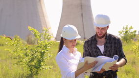 Close-up of two Builders with blueprints in hands. Male and female engineers discussing the construction plan drawings outdoors. Close-up of two Builders with stock video