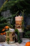 Close up. Two burning Christmas candles, surrounded by tangerines, branches of juniper and rosemary stock photo