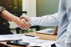 Close-up of two business executives shaking hands with data documents on the table.  royalty free stock photography
