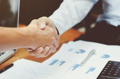 Close-up of two business executives shaking hands with data documents on the table royalty free stock photography