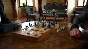 Close up of a two business men playing chess in an old fahioned restaurant stock footage