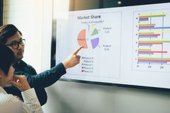 Close up two business people analysis chart working together at meeting room.  stock photography