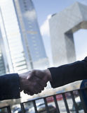 Close up of two business people shaking hands by the CCTV Building in Beijing Stock Photo