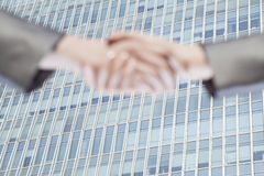 Close up of two business people shaking hands by Chinas world trade center in Beijing Royalty Free Stock Images
