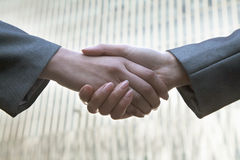 Close up of two business people shaking hands by Chinas world trade center in Beijing Stock Photography